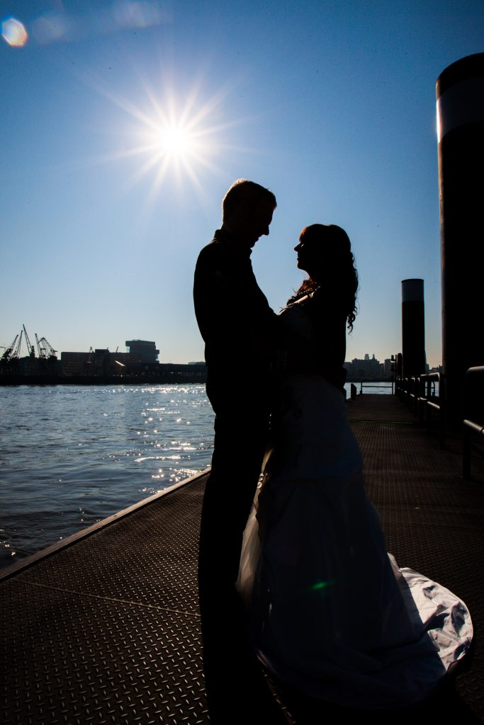 Silhouette of a couple romantically looking at eachother on the riverside under a sunny summer sky