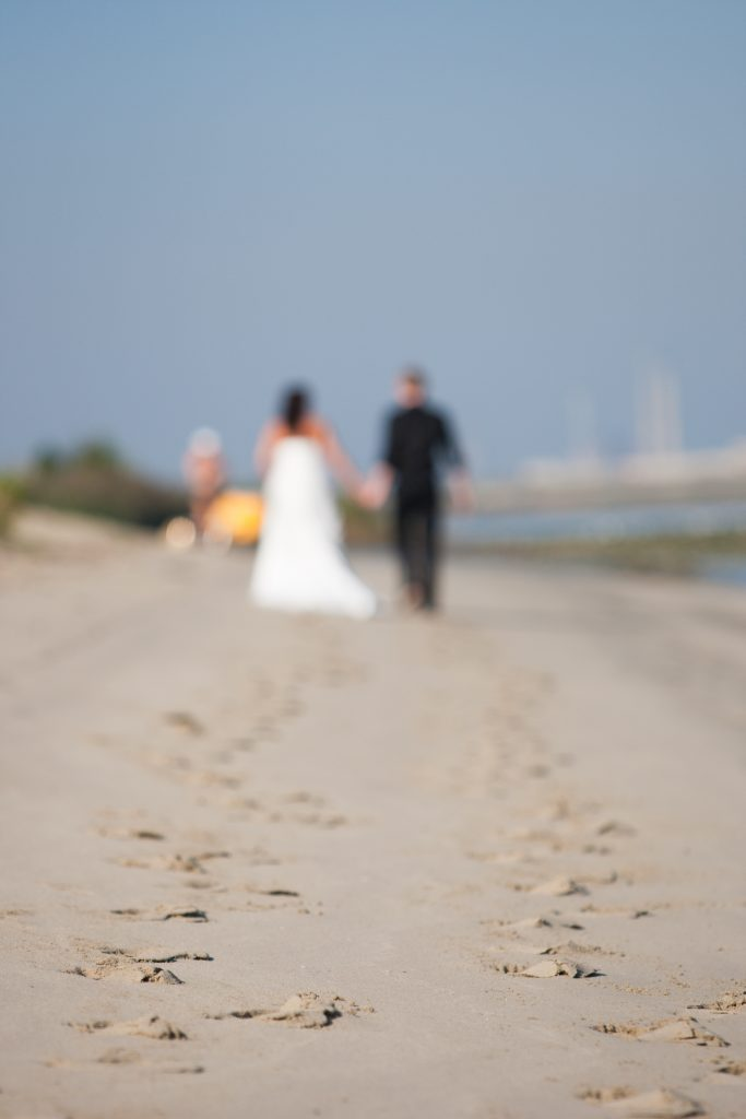 Unrecognizable out of focus newlywed couple walking on a beach with the focus on the footsteps in the sand on the foreground